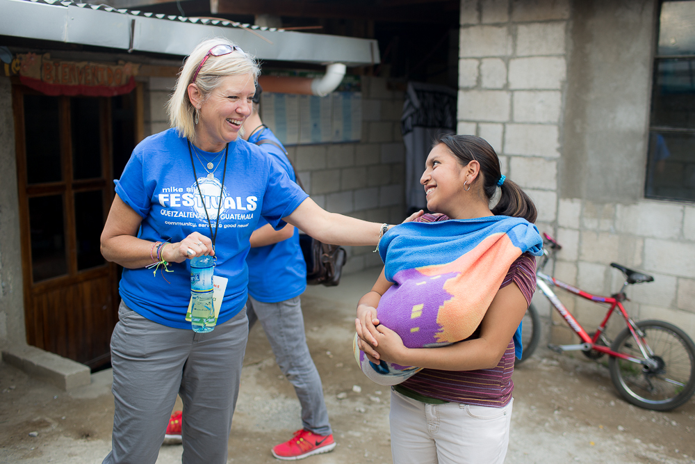 US team member and local woman greeting one another.